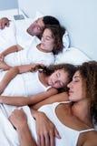 Família que dorme junto na cama imagens de stock