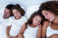 Família que dorme junto na cama foto de stock