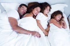 Família que dorme junto na cama fotografia de stock