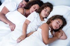 Família que dorme junto na cama fotografia de stock royalty free