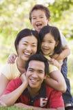 Família que encontra-se ao ar livre sorrindo imagem de stock royalty free