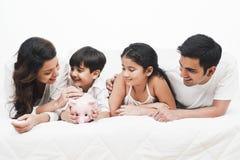 Família que encontra-se em uma cama Fotos de Stock Royalty Free
