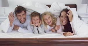 Família que encontra-se junto sob a cobertura no quarto em casa 4k vídeos de arquivo