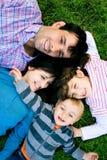 Família que encontra-se na grama Imagens de Stock Royalty Free