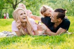 Família que encontra-se na grama no campo imagem de stock