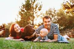 Família que encontra-se na grama no parque junto imagens de stock