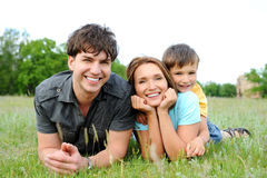 Família que encontra-se na grama verde foto de stock
