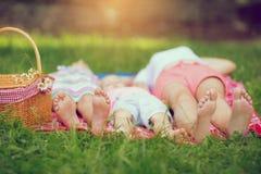Família que encontra-se na grama verde no parque imagem de stock