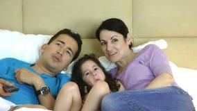 Família que encontra-se na televisão de observação da cama e que usa um telecontrole filme