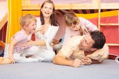 Família que encontra-se no assoalho fotografia de stock