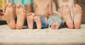 Família que encontra-se no junto-foco da cama em seus pés Fotografia de Stock Royalty Free