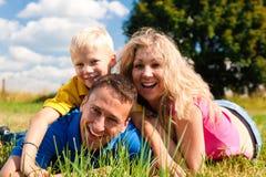 Família que encontra-se no prado Fotos de Stock