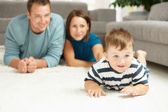 Família que encontra-se no tapete Fotografia de Stock Royalty Free