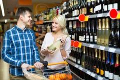 Família que escolhe o vinho na loja de alimento Fotografia de Stock