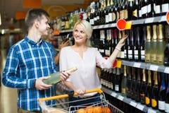 Família que escolhe o vinho na loja de alimento Imagem de Stock