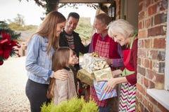 Família que está sendo cumprimentada por avós como chegam para a visita no dia de Natal com presentes imagem de stock royalty free
