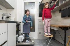 Família que esvazia a máquina de lavar louça Fotografia de Stock Royalty Free