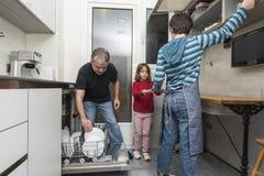 Família que esvazia a máquina de lavar louça Fotos de Stock Royalty Free