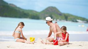 Família que faz o castelo da areia na praia branca tropical Gene e duas meninas que jogam com a areia na praia tropical video estoque