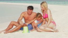 Família que faz o castelo de areia no feriado da praia vídeos de arquivo