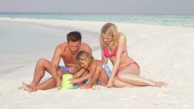 Família que faz o castelo de areia no feriado da praia filme
