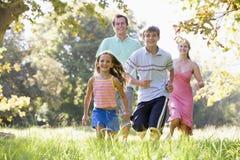 Família que funciona ao ar livre o sorriso Fotos de Stock Royalty Free