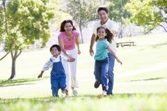 Família que funciona ao ar livre prender as mãos e sorrir fotografia de stock