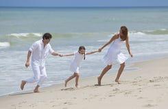 Família que funciona e que tem o divertimento na praia Foto de Stock Royalty Free