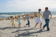 Família que funciona na praia Imagens de Stock Royalty Free