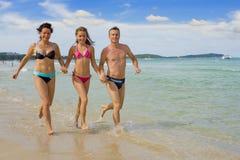 Família que funciona na praia Imagem de Stock Royalty Free
