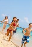 Família que funciona na praia foto de stock royalty free