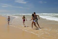 Família que funciona na praia Fotos de Stock Royalty Free