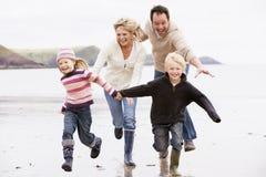 Família que funciona nas mãos da terra arrendada da praia Imagens de Stock