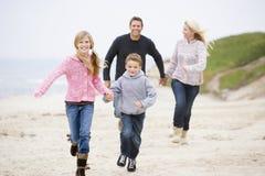 Família que funciona nas mãos da terra arrendada da praia Fotografia de Stock