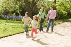 Família que funciona no sorriso das mãos da terra arrendada do trajeto Imagens de Stock Royalty Free