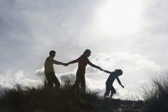 Família que guarda as mãos ao andar na praia imagens de stock royalty free