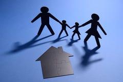 Família que guarda as mãos com a casa do enigma de serra de vaivém Fotos de Stock Royalty Free