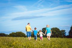 Família que guarda as mãos que correm sobre o prado Imagens de Stock Royalty Free