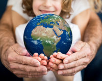 Família que guarda o planeta da terra nas mãos Imagens de Stock