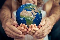 Família que guarda o planeta da terra nas mãos Imagens de Stock Royalty Free