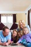 Família que joga com computador da tabuleta em casa Fotografia de Stock