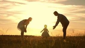 Família que joga com sua filha nos raios do sol o bebê vai do paizinho à mamã e aos risos Movimento lento Mam? e paizinho video estoque