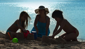 Família que joga na praia - silhuetas imagens de stock royalty free