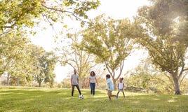 Família que joga o futebol no parque junto fotos de stock royalty free