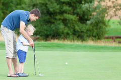 Família que joga o golfe imagens de stock
