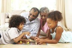 Família que joga o jogo de mesa em casa Fotografia de Stock