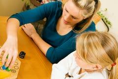 Família que joga um jogo de mesa Fotografia de Stock Royalty Free