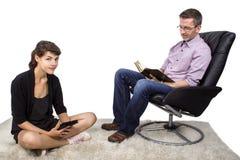 Família que lê em casa Fotos de Stock Royalty Free