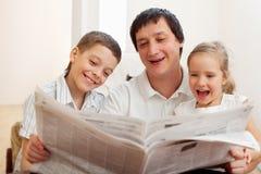 Família que lê um jornal Fotografia de Stock Royalty Free
