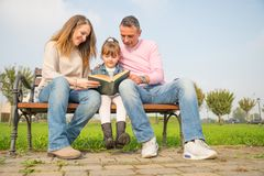 Família que lê um livro Foto de Stock Royalty Free